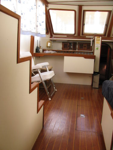 Portside salon with bar over galley, teak & holly sole