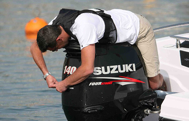 Man working on outboard engine