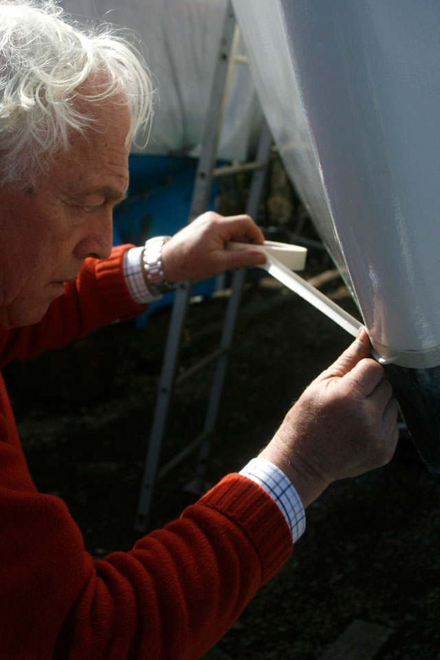Using masking tape to prepare yacht before antifouling