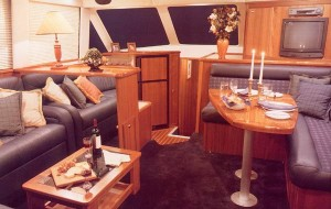The salon of the Riviera 43 includes complete dining and entertaining arrangements, as well as a cabinet-mounted TV/VCR.