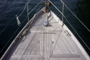 A photo of the teak deck on the foredeck of a sailboat.