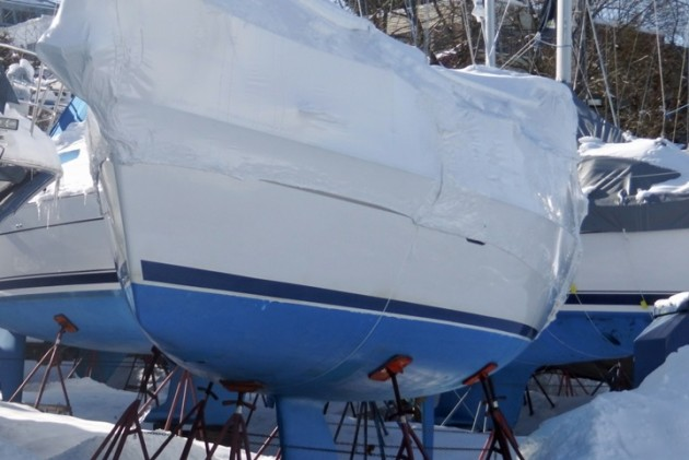 This boat is properly supported by stands, and the shrink-wrap is pitched steeply enough to let melting snow slide off.