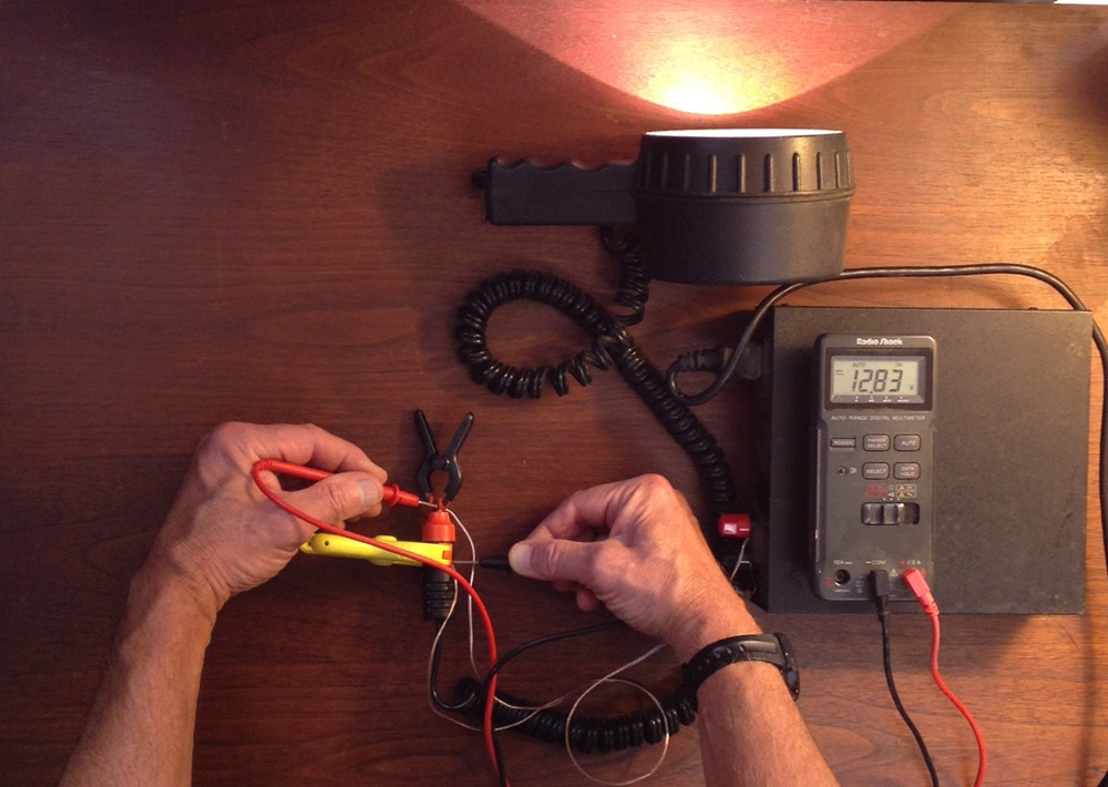 Fig. 4 -  When the light is connected to the power supply by undersized wires, there's an 8.4% drop in voltage – and those undersized wires get quite warm. Also note the reduced output of the light.