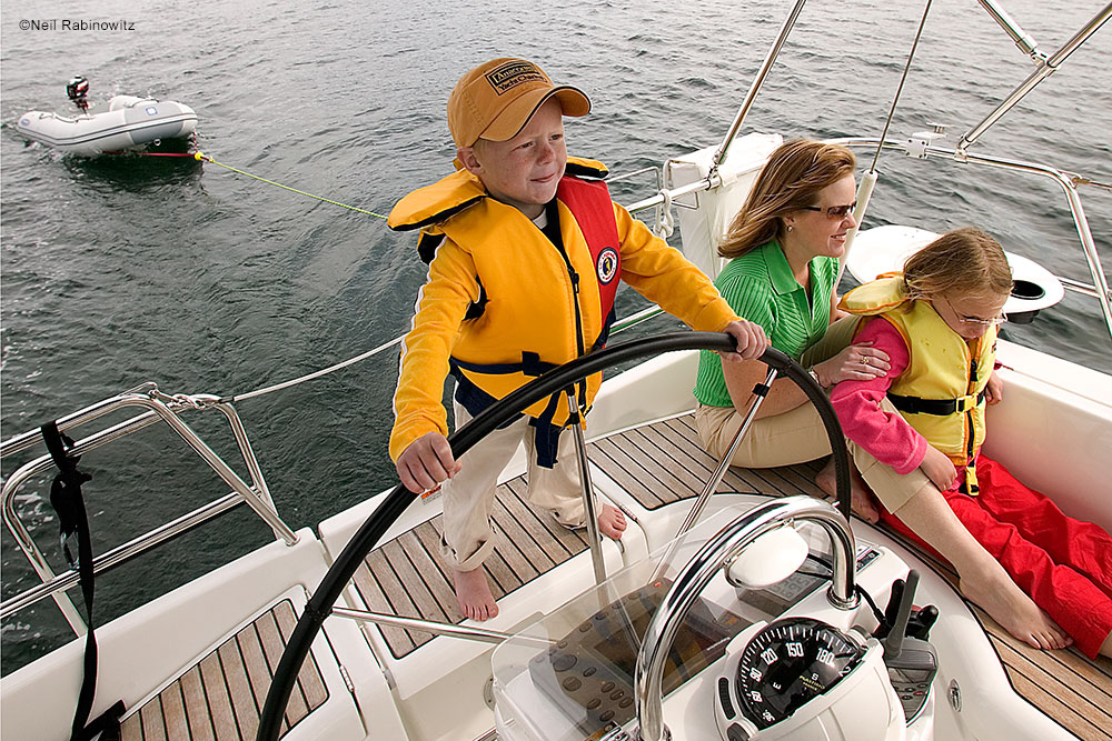 kids steering sailboat