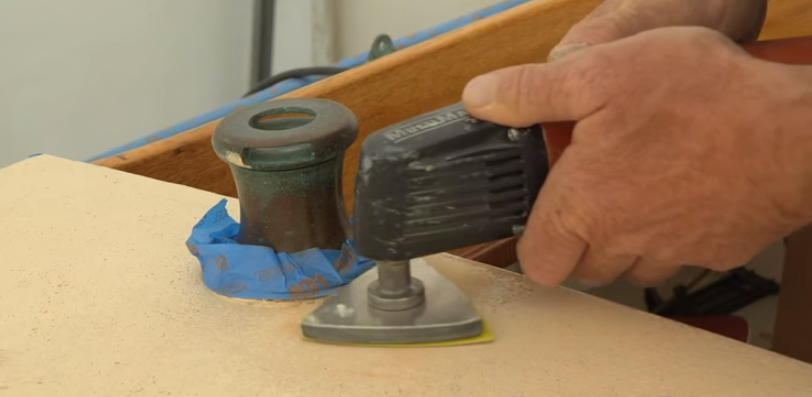 A trim sander will be able to get closer to deck-mounted hardware than a disc or random-orbital sander.