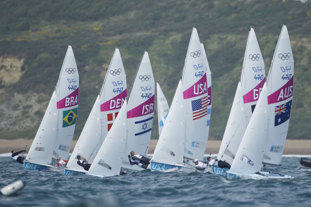 At the beginning of a race, the fleet of boats such as these 470 class two-person dinghies, is usually closely spaced. Each competitor has tried to cross the starting line at full speed exactly as the five-minute starting countdown reaches zero. Photo OnEdition.