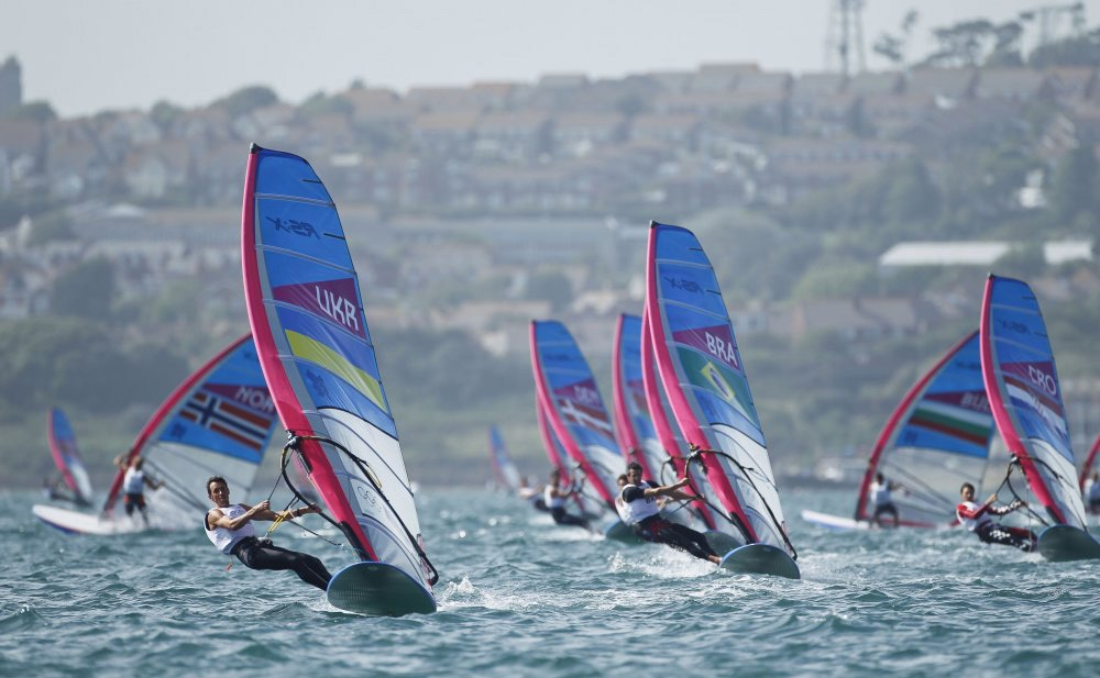 Sailors must trim their sails to take advantage of wind power as they sail around a racecourse. On some of the boats, such as the Olympic RS:X windsurfer class, kinetic power is allowed, and sailors can literally fan their boats forward by pumping their sails, which is a rigorous physical challenge.  Photo OnEdition.
