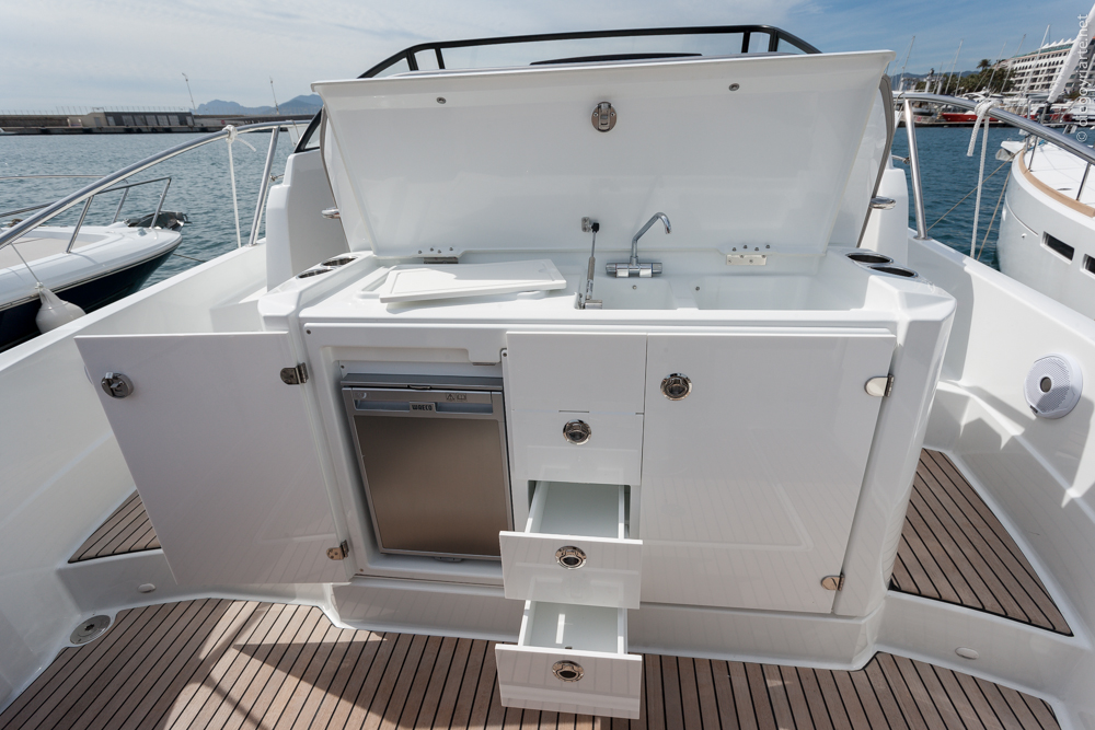 The outdoor galley has everything you need: a double sink, counter, the option of installing an electric grill, a refrigerator, and plenty of stowage. It's slightly raised; a single step that improves the view from the helm as well as the headroom below deck.