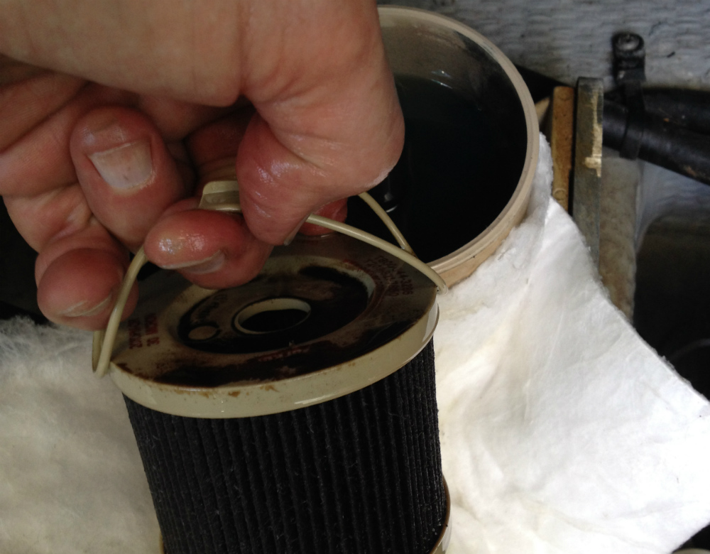 A foul 30-micron element emerges from a Racor fuel filter. Note the almost black color of the fuel in the bowl. The microorganisms have been hard at work in this fuel system.
