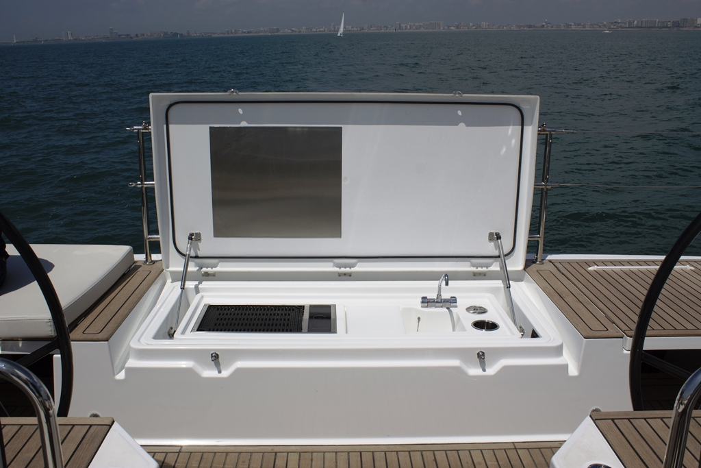 The entire teak-topped transom is a sunpad that hides a galley module below. An electrically raised grill, sink, and prep station pop out of the transom, and a 42-quart mini-fridge is at cockpit sole height next to the port wheel.