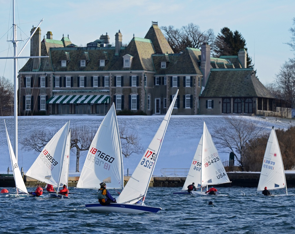 Laser Fleet 413 races on a brisk day with the snowy lawn of the New York Yacht Club as a back drop; the racers launch out of the Sail Newport drysail area, just across the cove. Jeff Stevens photo.