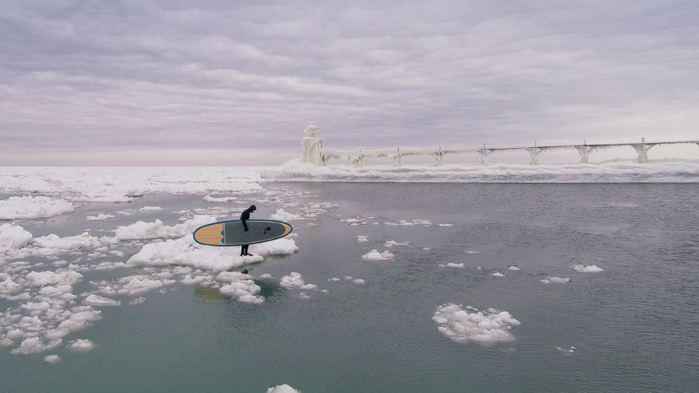 Paddleboarder Karol Garrison contemplates his own private iceberg in the icy world of the lighthouse and breakwater at the western Michigan entrance to the St. Joseph's River. Photo by Seth Haley/sethhaley.com.