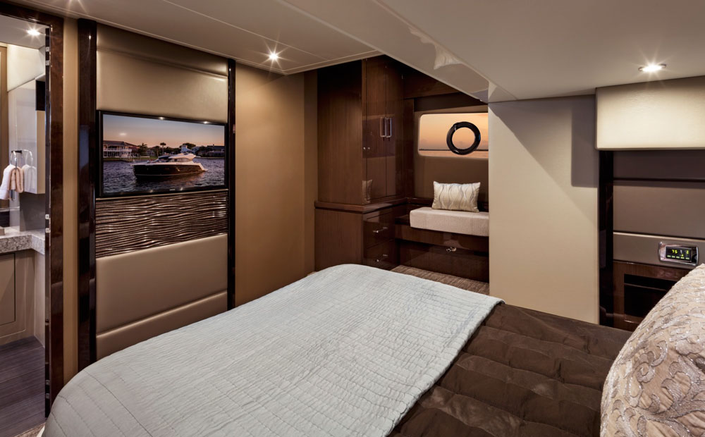 Dark tan upholstery and wall coverings along with dark, rich, glossy cabinetry give the master stateroom a luxurious and modern vibe.
