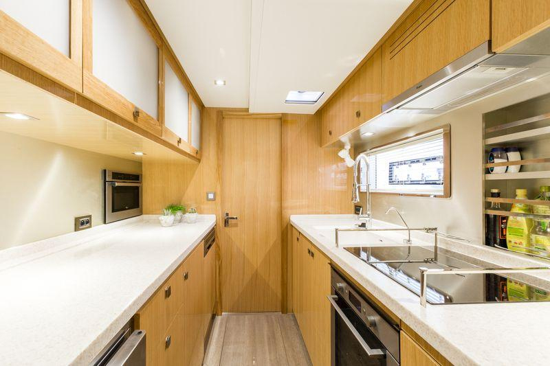 The galley features a large glass cooktop outboard, flanked on one side by a house-sized sink and on the other by ample countertops laid over numerous cupboards and soft-close drawers.