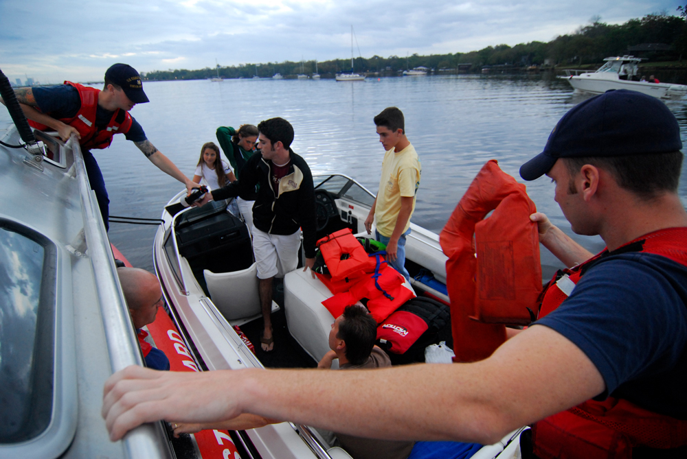 Some safety gear is mandated and other gear is not. Here, the USCG checks a recreational boat to be sure the minimum requirements are met. Photo by Petty Officer 1st Class Bobby Nash, courtesy of USCG.