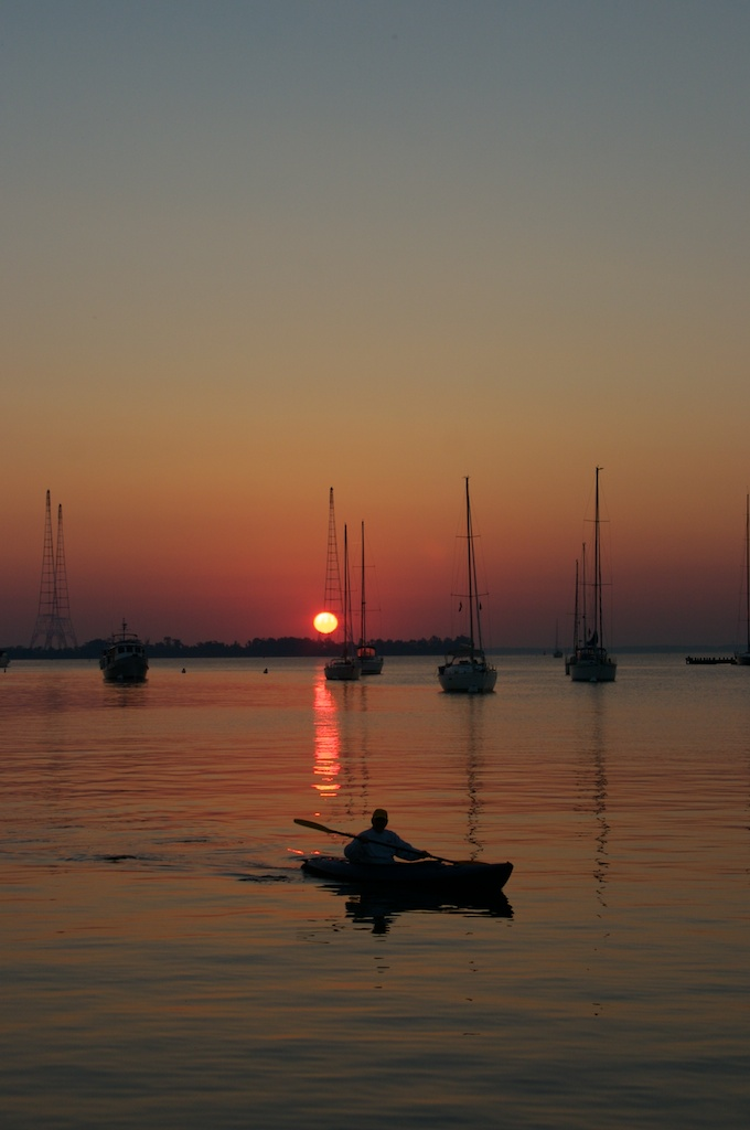The sun rise over the Chesapeake Bay and Annapolis Harbor as a lone kayaker glides by.