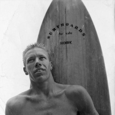 A photo of Hobie Alter in front of one of his early surfboards.