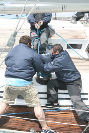 Three sailors trim the jib