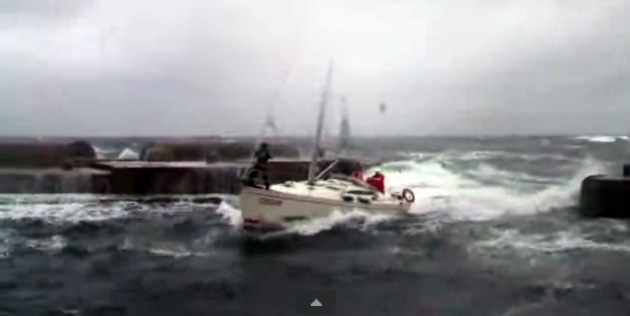 Sailboat surfs through breakwater opening