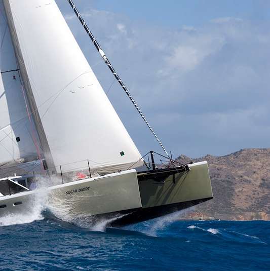 Sugar Daddy, a Gunboat catamaran, launches off a warm wave off St. Maarten.