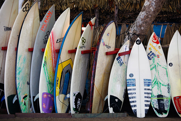 many surfboards lined up near beach hut